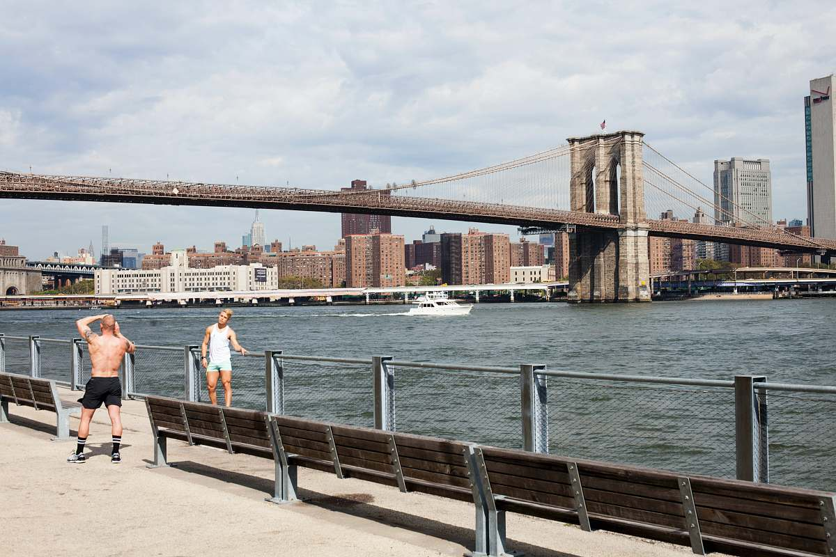 stock photos free  of human two men taking picture in front of Brooklyn Bridge people