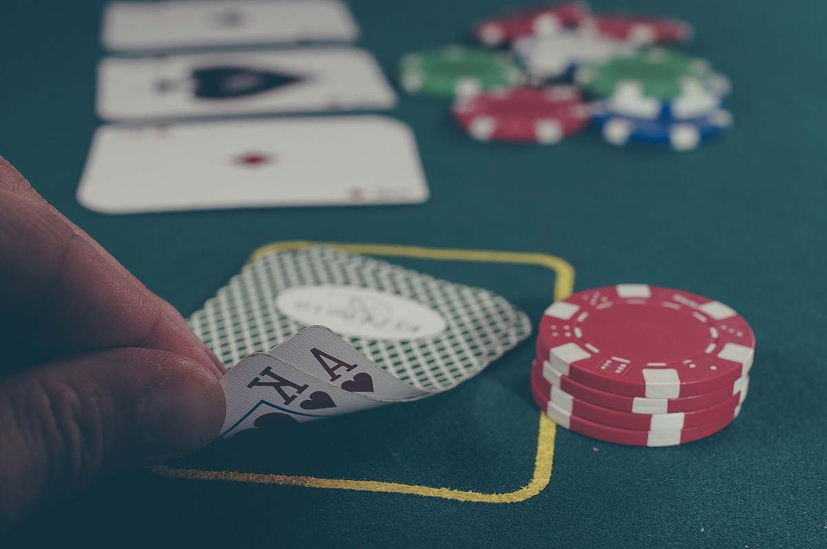 gambling person holding black ace and king spades playing cards on poker table game