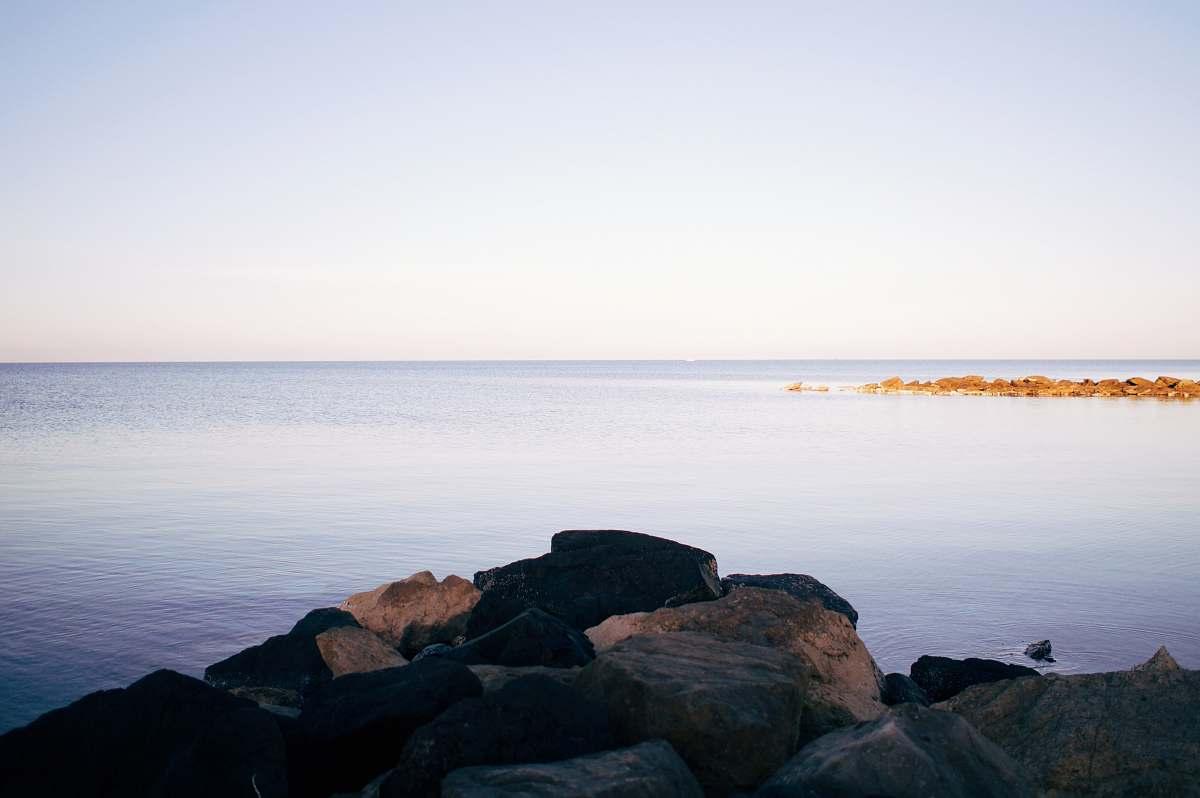 stock photos free  of shoreline rocks beside body of water water