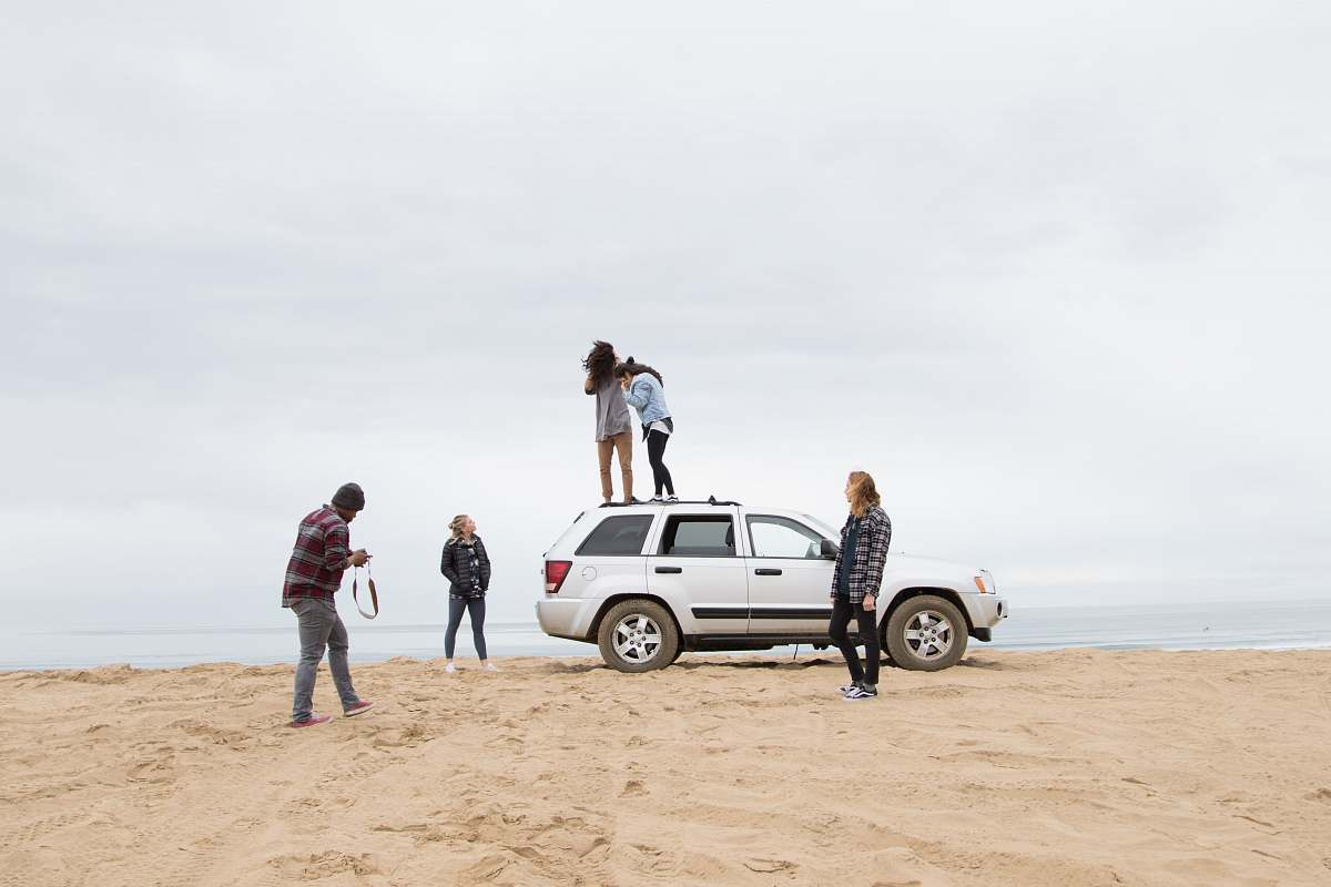 stock photos free  of car two people standing on Jeep Grand Cherokee SUV while the other person camera on sand during daytime transportation