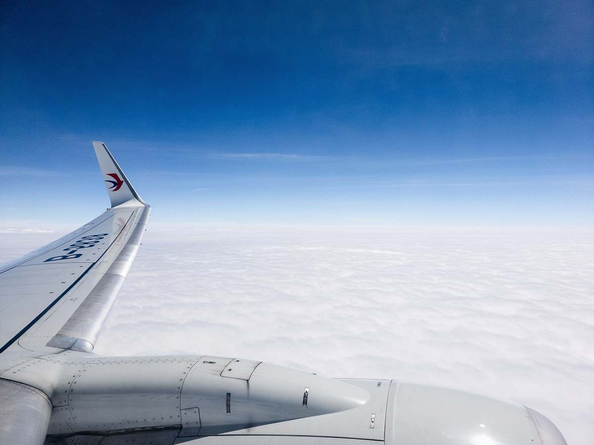 stock photos free  of airplane aerial photo of plane flying above clouds under clear blue sky transportation