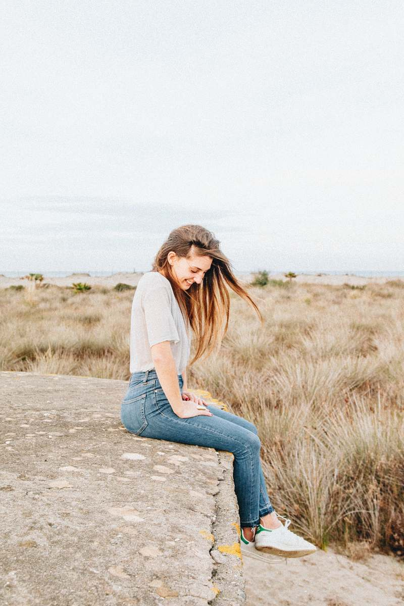 stock photos free  of person laughing woman sitting on concrete surrounded by brown grass people