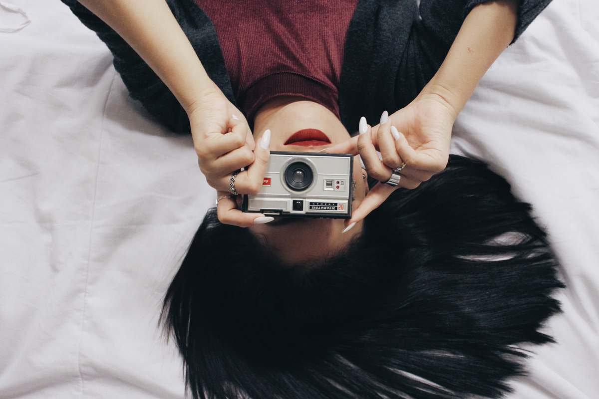 stock photos free  of camera lying woman in red and black top holding silver point and shoot camera human