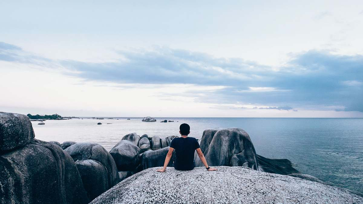 stock photos free  of people man sitting on rock beside body of water sea