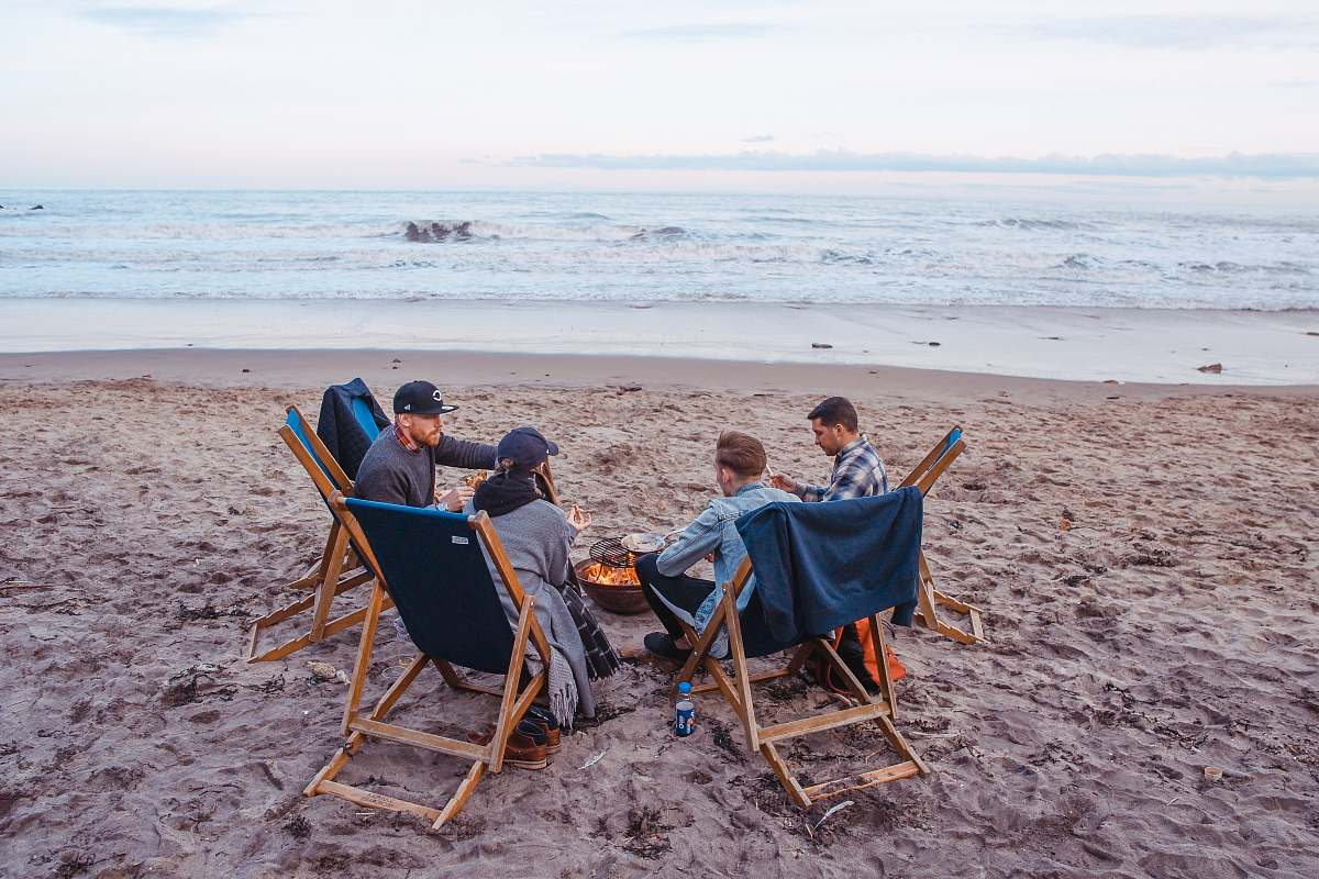 People Three Men And One Woman Sitting On Beach Lounge In Front Fire Pit Near Seashore Human Image Free Stock Photo