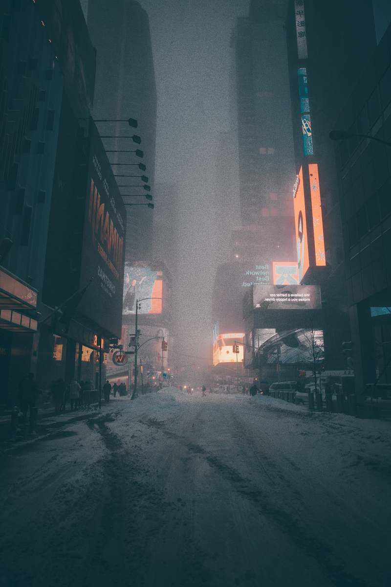 stock photos free  of snow people walking on street surrounded by city buildings during nighttime blizzard