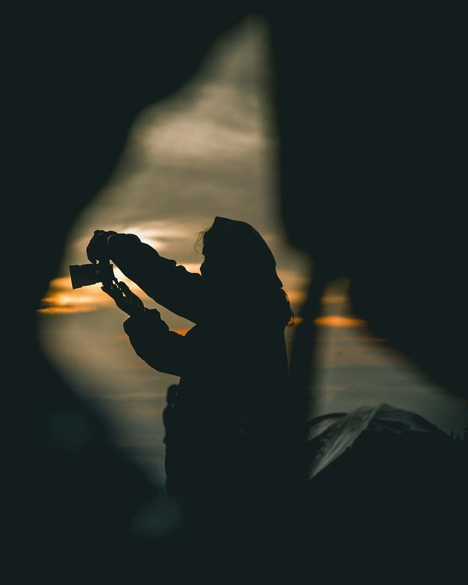 stock photos free  of human silhouette of person holding camera during orange sunset person