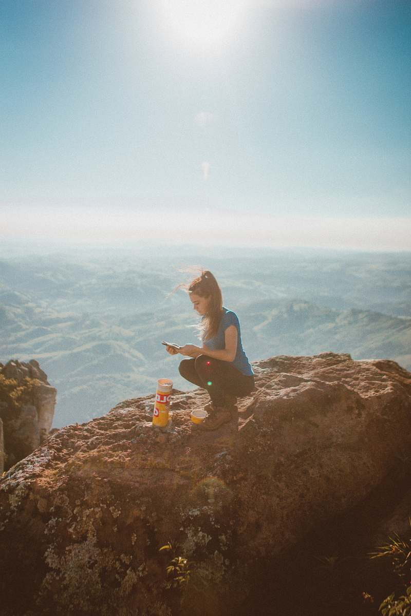 stock photos free  of person woman holding smartphone while sitting beside orange bottle on top of rock formation human