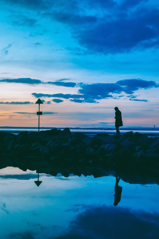 water silhouette of person walking on rocks near body of ...