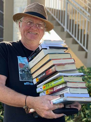 clothing man holding pile of books while smiling human