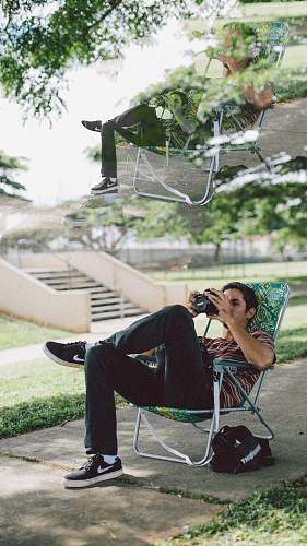 clothing man sitting on folding chair using DSLR camera footwear