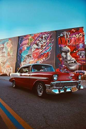 car red classic car parked beside wall with graffiti transportation