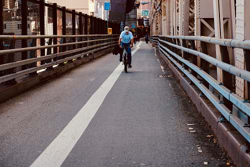 human man riding bicycle in bridge person