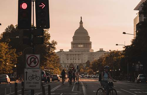 bike people biking on road and different vehicles viewing United States Capitol during daytime screenshot transportation