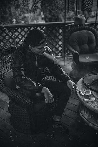 furniture greyscale photography of man sitting on the chair smoking chair
