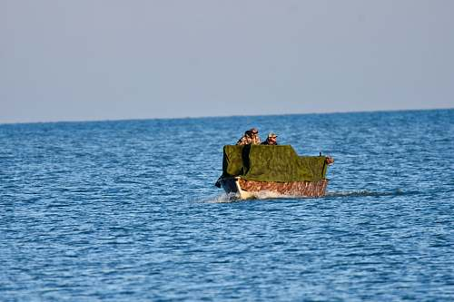 transportation green and brown boat on body of water during daytime vehicle