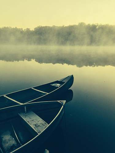 transportation two gray canoes on misty body of water canoe