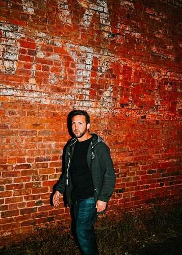 apparel man in black zip-up hoodie walking beside brown bricked wall clothing
