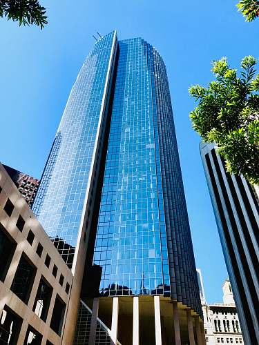 city low angle photo of blue glass curtain building office building
