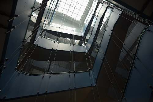 architecture low-angle photography of multi-storey building with glass ceiling window
