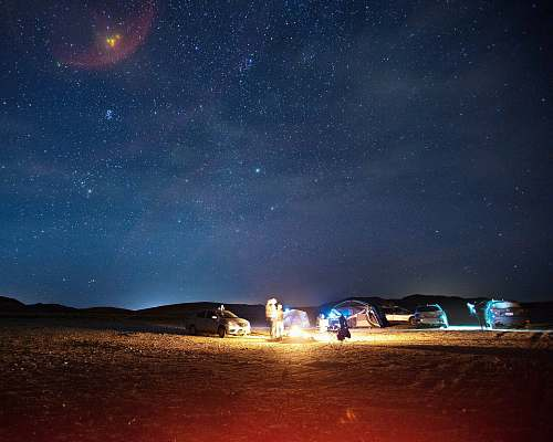 night lighted fire near car and dome tent during night time milky way