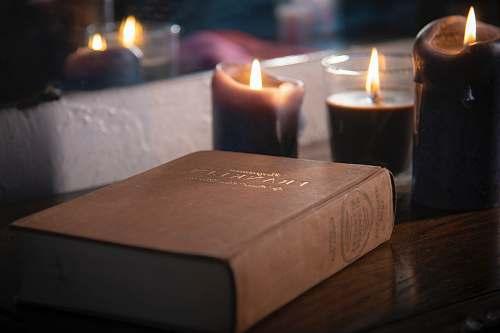 fire brown hardbound book near lighted pillar candles laurelton