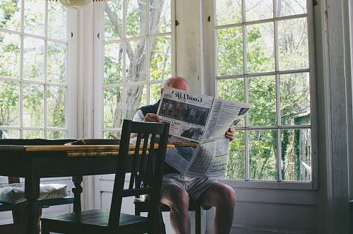 furniture man reading newspaper while sitting on chair window