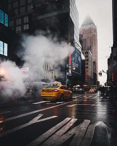 photo cab yellow taxi sedan on gray concrete street passed through white smokes near walking lane taxi free for commercial use images