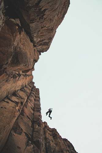 outdoors person climbing mountain during daytime vantage