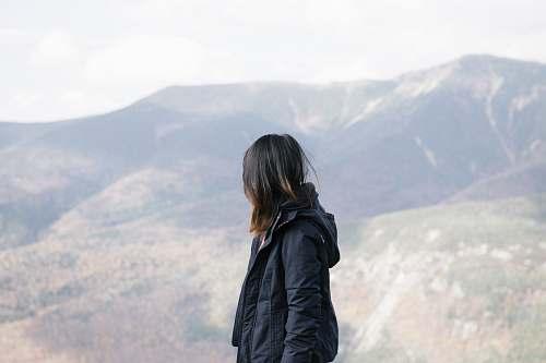 jacket person wearing black jacket leaning mountain during daytime apparel