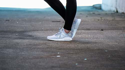 apparel shallow focus photo of person wearing gray running shoes shoe