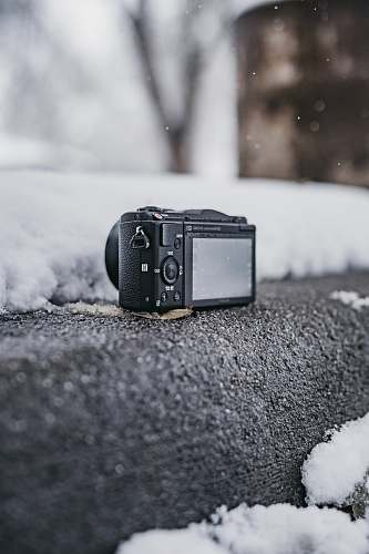 electronics black point-and-shoot camera on gray surface outdoor camera