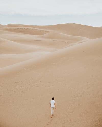desert person walking on sand dune sand