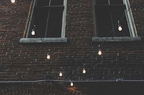 brick two brown windows near black string lights denver
