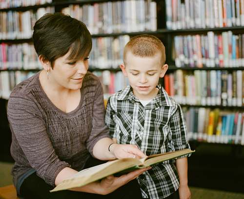 person boy in gray sweater beside boy in gray and white plaid dress shirt book