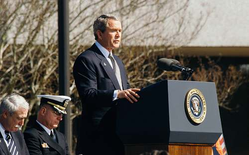 person George W. Bush standing on lectern during daytime speech