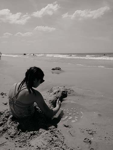 person grayscale photography of woman sitting in beach back