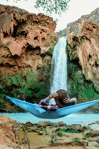 person man laying on blue hammock in front of waterfalls hammock