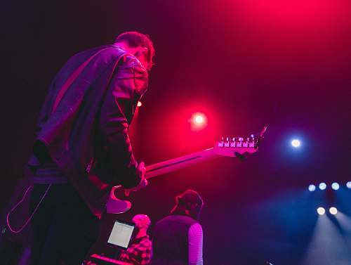 person man playing guitar on stage lighting