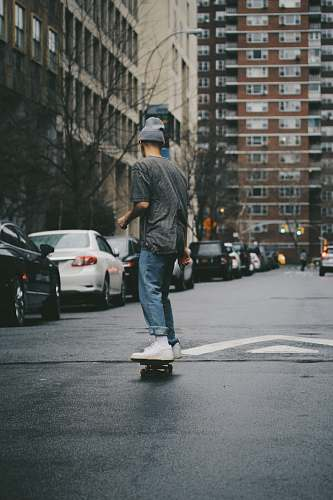 person man riding skateboard near high rise building people