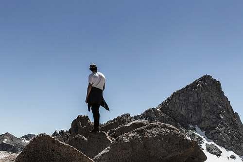 person man standing on rock mountain peak people