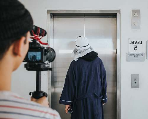 person person filming man standing near elevator inside room people