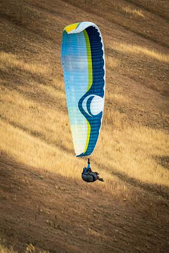 person person hanging on white and blue parachute adventure