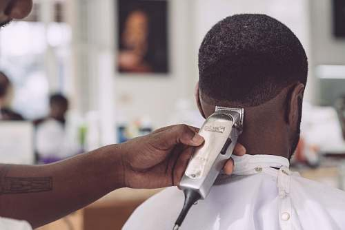 person person holding hair clipper cutting the hair of man sitting people