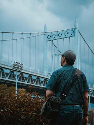 person person standing and looking at gray metal bridge people