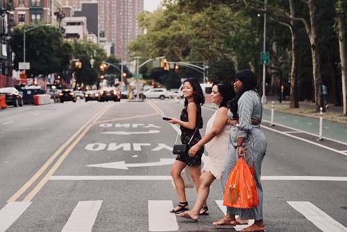 person three women walking on pedestrian lane people