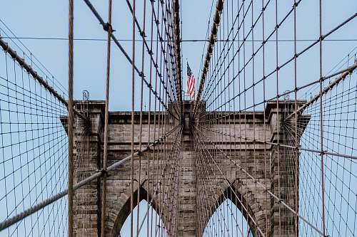 person USA flag on Brooklyn Bridge during daytime people
