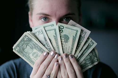 person person holding fan of U.S. dollars banknote people