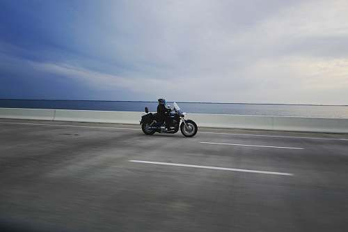vehicle person riding touring motorcycle on gray concrete road transportation