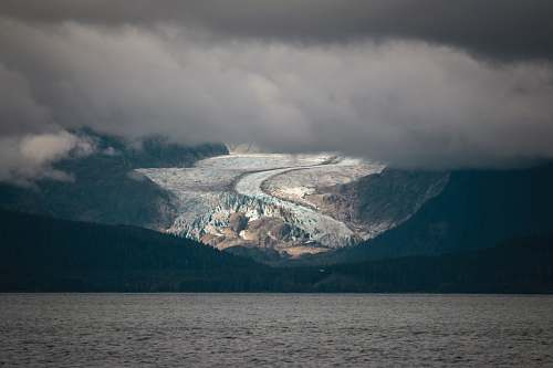 glacier body of water near mountains ice